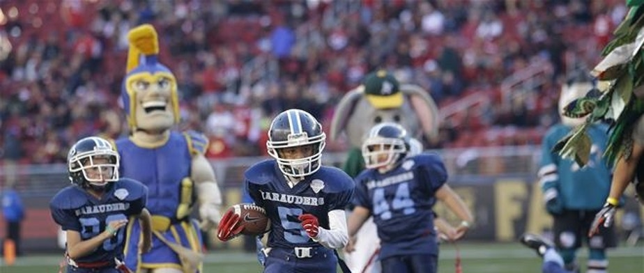 In this Nov. 29, 2015, file photo, San Jose Marauders youth football players play sports mascots during halftime of an NFL football game between the San Francisco 49ers and the Arizona Cardinals in Santa Clara, Calif.