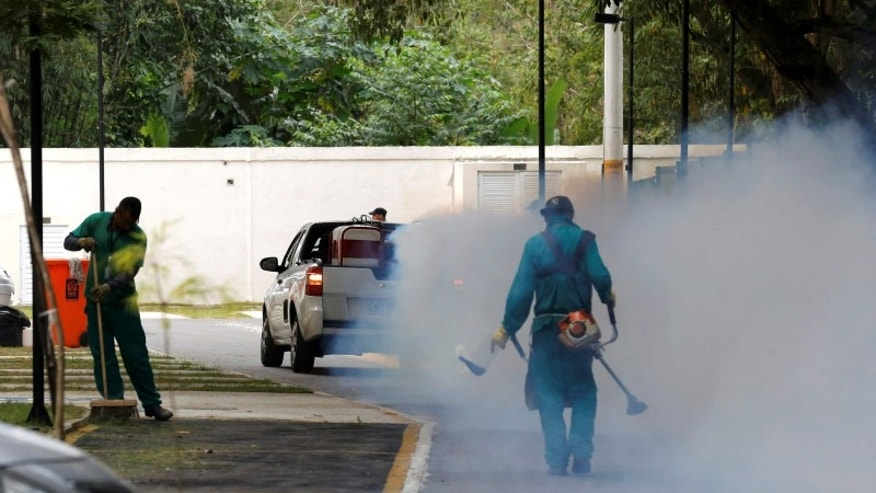 A truck sprays insecticide around Olympic media accomodations in Rio de Janeiro