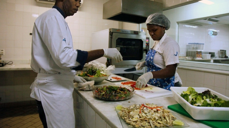 FILE - In this May 6, 2016, file photo, cooks prepare meals during one of many food-testing exercises of the Olympic menu in Rio de Janeiro, Brazil. The caloric intakes for athletes in certain sports as they train for major competitions like what awaits in Rio are massive, several times more than what the typical adult needs to get through a regular day. (AP Photo/Renato Spyrro, File)