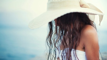 Pretty girl in bikini looks beautiful on the beach in a bikini and hat while her long wet curly hair falling over her face. In the background is horizont over the sea