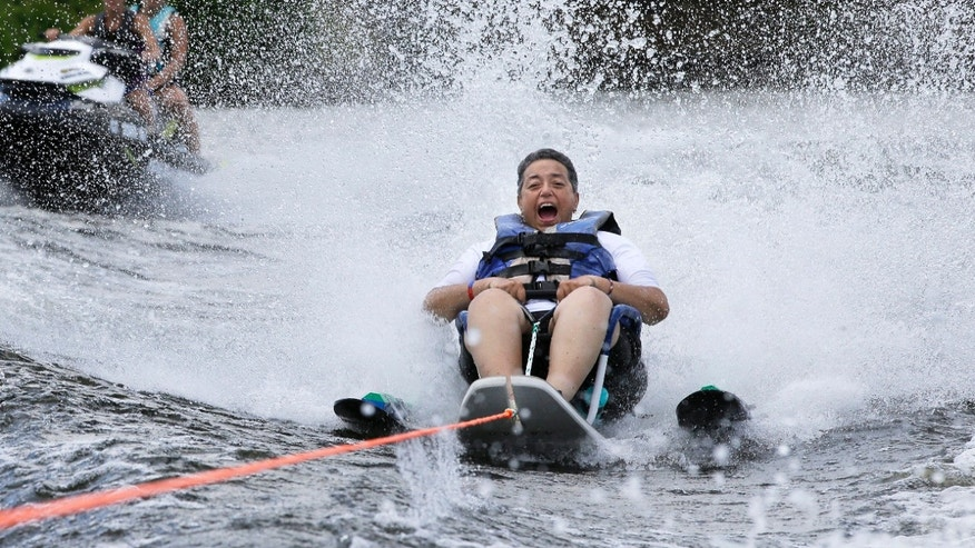 In this Tuesday, July 19, 2016 photo U.S. Navy veteran Raquel Ardin, of North Hartland, Vt., who suffered a broken neck while serving in the Navy, water skis during a rehabilitation clinic in Coventry, R.I. The Providence VA Medical Center hosted the four-day clinic for veterans with spinal cord injuries, amputations, visual impairments, neurological problems and other disabilities where they were able to go water skiing, kayaking, and sailing.
