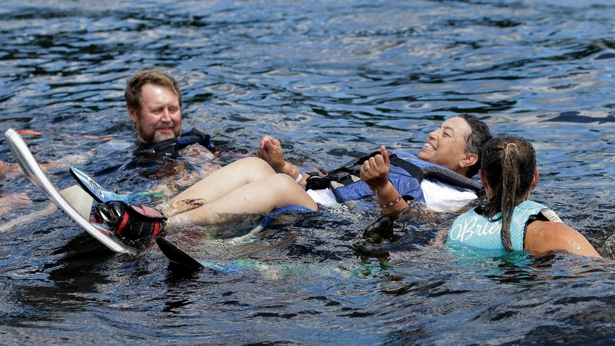 U.S. Navy veteran Raquel Ardin, of North Hartland, Vt., center, who suffered a broken neck while serving in the Navy, is assisted by volunteers while water skiing during a rehabilitation clinic, in Coventry, R.I.
