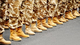 Soldiers feet in desert camouflage military uniform in rest position