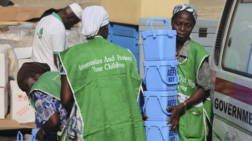 Local health workers carry vaccination kits at a distribution centre ahead of the start of a nationwide polio immunization campaign on Wednesday, in Lagos