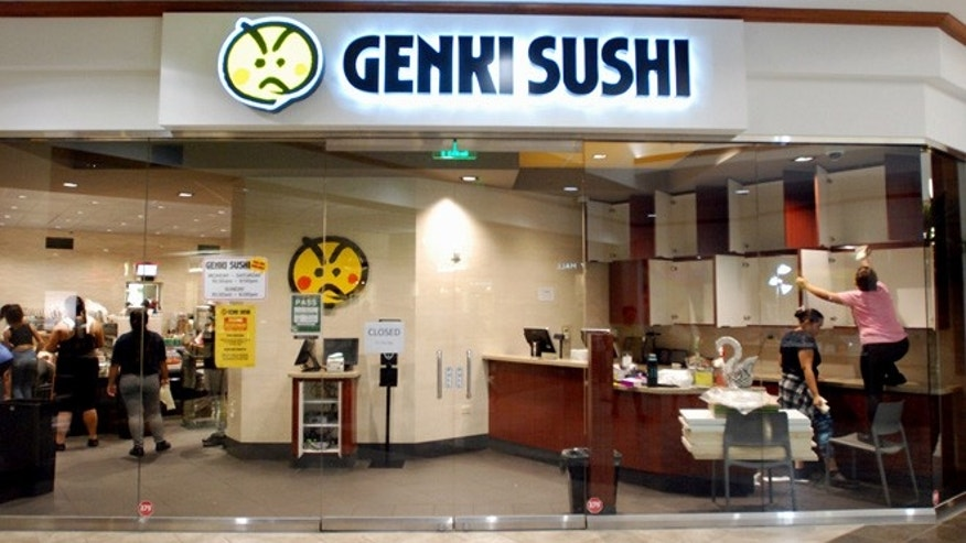 Employees clean the Genki Sushi conveyor belt restaurant chain Tuesday, Aug. 16, 2016, in Aiea, Hawaii.