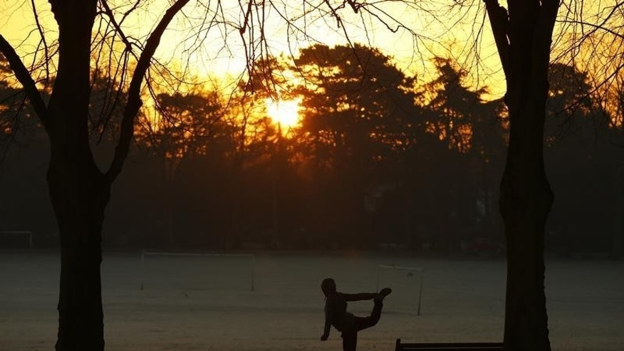 A woman exercises as the sun rises over Victoria Park in Leicester