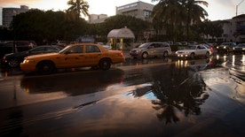 Palm trees are reflected in puddles after a torrential downpour in the South Beach part of Miami, July 18, 2014.         REUTERS/Carlo Allegri (UNITED STATES - Tags: SOCIETY ENVIRONMENT) - RTR3ZAR7