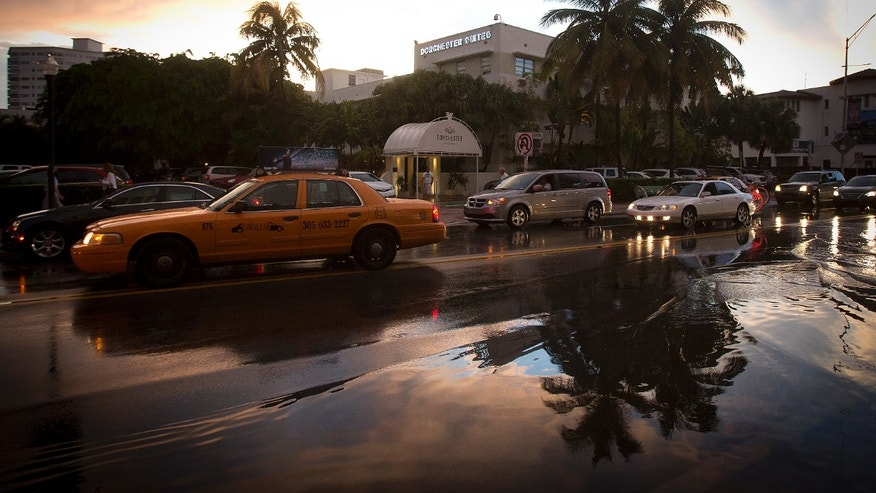 Palm trees are reflected in puddles after a torrential downpour in the South Beach part of Miami, Florida.