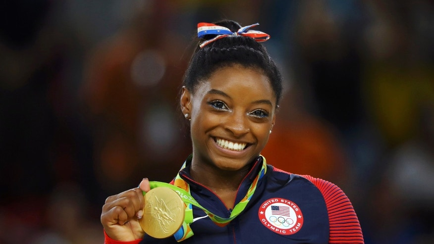 Simone Biles (USA) of USA poses with her gold medal on the podium.