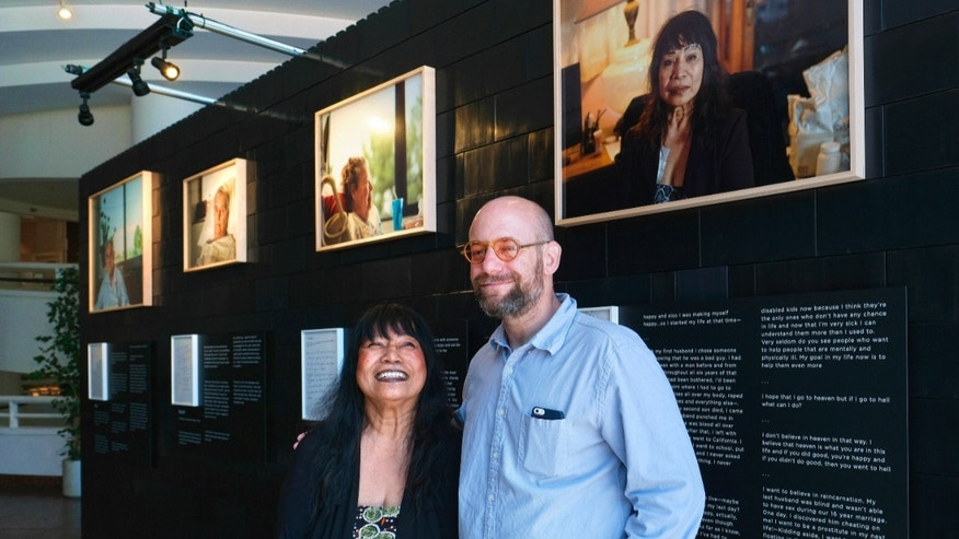 "In this Aug. 15, 2016 photo, photographer Andrew George, right, poses with Nelly Gutierrez, who is featured in George's exhibit, ""Right, Before I Die,"" at the Museum of Tolerance in Los Angeles. The exhibit, which features portraits of people facing serious illnesses, will run until Sept. 30."