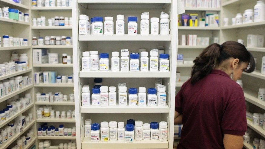 A pharmacy employee looks for medication as she works to fill a prescription while working at a pharmacy in New York December 23, 2009.