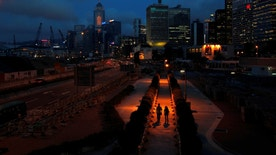 People walk on a pavement at Hong Kong's financial Central district during sunset May 11, 2011.   REUTERS/Bobby Yip/File Photo - RTX2KU21