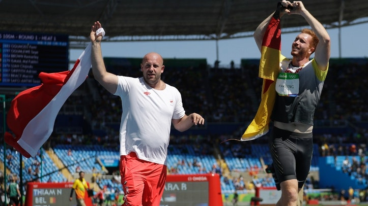 Poland's silver medal winner Piotr Malachowski, left, and Germany's gold medal winner Christoph Harting celebrate with their countries' flags after the men's discus throw final during the athletics competitions of the 2016 Summer Olympics at the Olympic stadium in Rio de Janeiro, Brazil, Saturday, Aug. 13, 2016. (AP Photo/Matt Dunham)