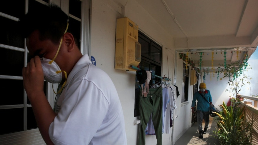 A National Environment Agency officer informs residents as a worker fogs the corridor of a public housing estate in the vicinity where a locally transmitted Zika virus case was discovered, in Singapore August 29, 2016.