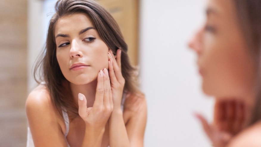 woman looking at skin in mirror istock
