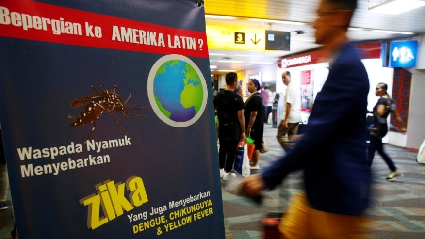 Passengers arriving from Singapore walk near a banner about Zika virus at the Soekarno-Hatta airport in Jakarta
