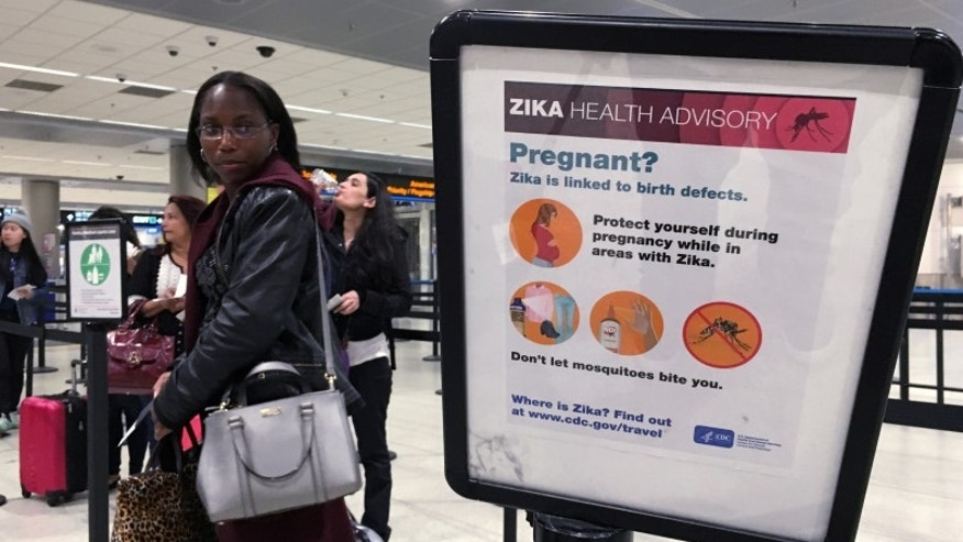 A woman looks at a Center for Disease Control (CDC) health advisory sign about the dangers of the Zika virus as she lines up for a security screening at Miami International Airport in Miami