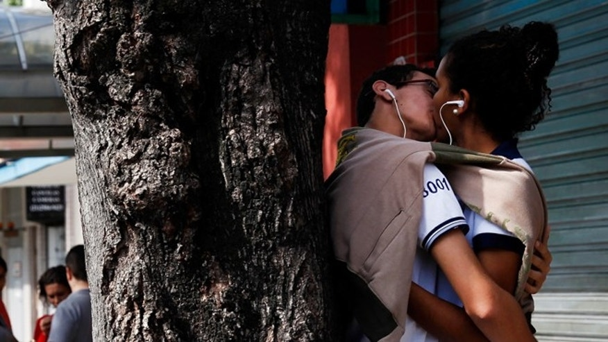 RIO DE JANEIRO, BRAZIL - JUNE 11:  A couple kisses as people watch on Rue Pererra Nunes as the 2014 FIFA World Cup nears on June 11, 2014 in Rio de Janeiro, Brazil.  (Photo by Jamie Squire/Getty Images)