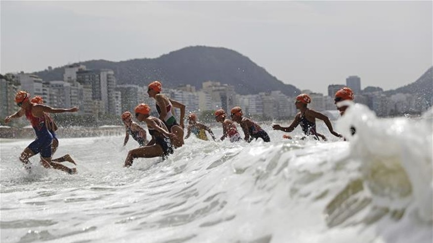 Competitors exit the water as they transition from the swim to bike portion of the women's triathlon event at the 2016 Summer Olympics in Rio de Janeiro, Brazil.