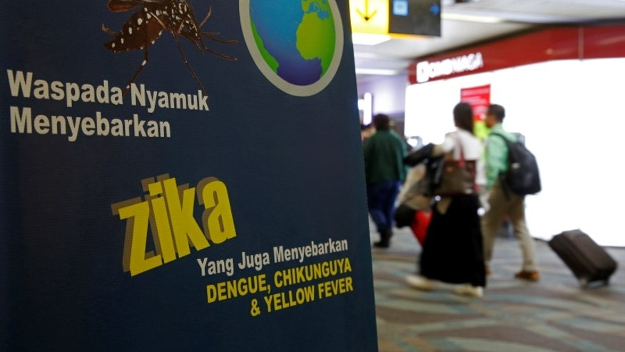 Airline passengers walk past a banner about the Zika virus shortly after landing from Singapore at Soekarno-Hatta airport in Jakarta