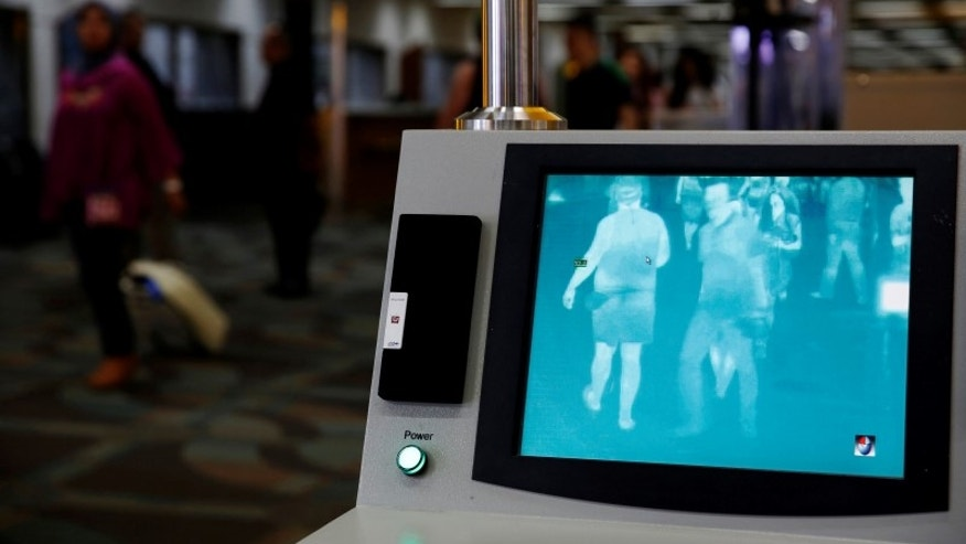 Airline passengers walk past a thermal scanner for body temperature shortly after landing from Singapore at Soekarno-Hatta airport in Jakarta