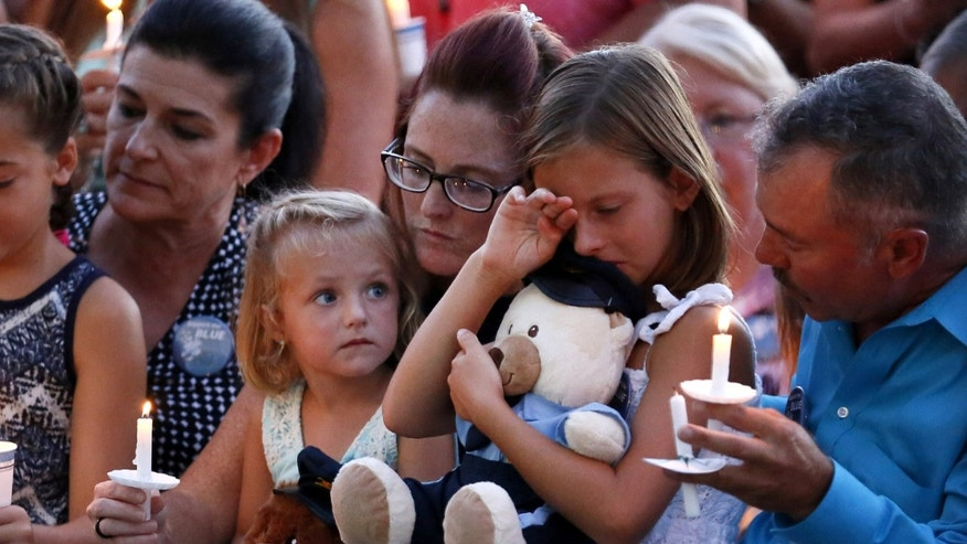Dechia Gerald, wife of slain officer Matthew Gerald, holds her two daughters at a vigil in Baton Rouge, Louisiana, U.S. July 18, 2016.  REUTERS/Jonathan Bachman - RTSIM76