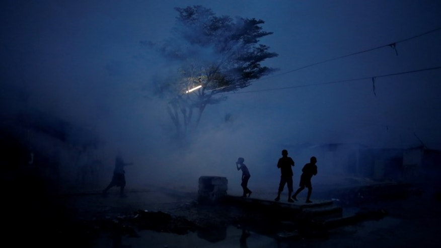 Residents are seen as workers of the Ministry of Public Health and Population fumigate in the street against mosquito breeding to prevent diseases such as malaria, dengue and Zika, during a fumigation campaign in Port-au-Prince, Haiti
