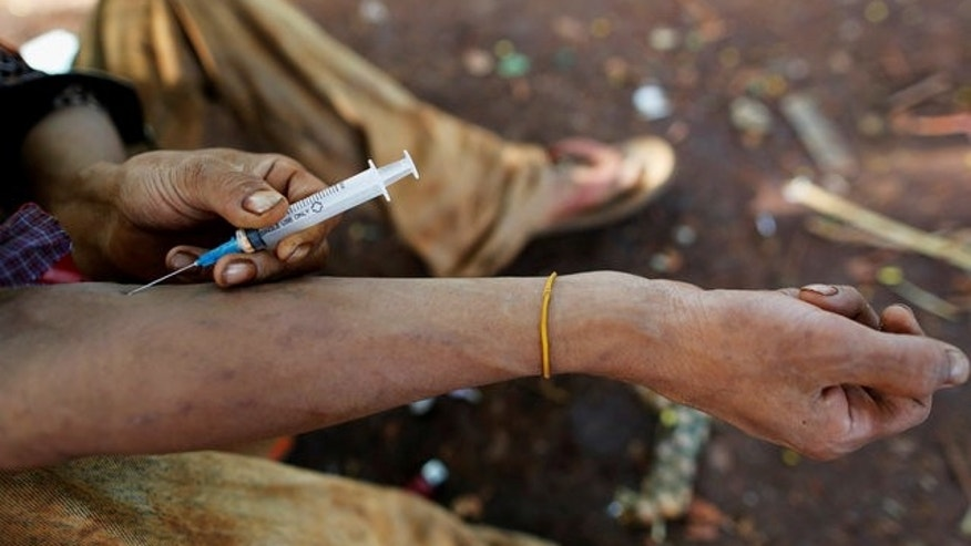 A man injects heroin into his arm along a street in Man Sam, northern Shan state, Myanmar