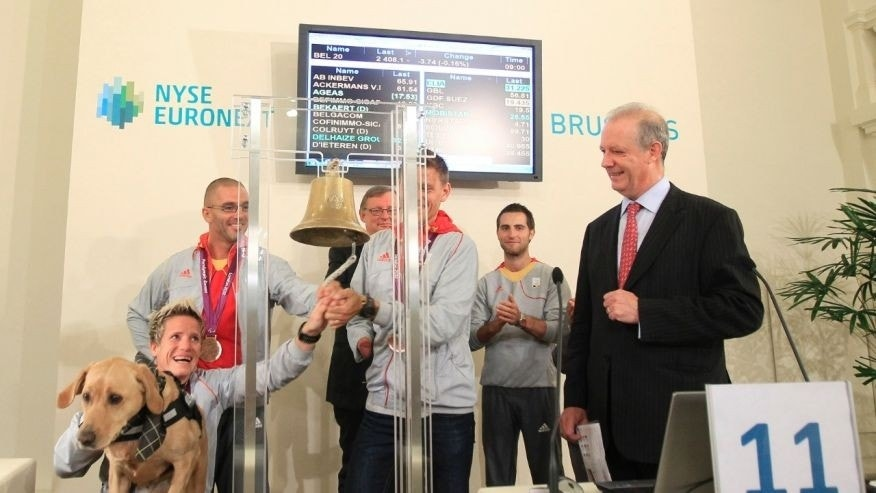Belgian athlete Marieke Vervoort (L) rings a bell in the presence of fellow athletes Wim Decleir (back L) and Frederic Van den Heede (C), NYSE Euronext Brussels CEO Vincent Van Dessel (R) and her dog Zenn, after their return from the London 2012 Paralympic Games at the Brussels stock exchange building September 11, 2012.