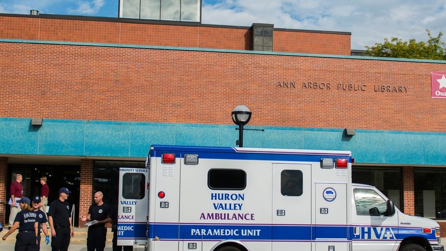 In this September 9, 2014 file photo, Ann Arbor police, firemen, and medical personnel respond to an overdose at the Ann Arbor District Library in Ann Arbor, Mich.  Librarians are finding themselves face-to-face with the heroin and opiod epidemic as drug users take advantage of the free access to quiet areas where people often keep to themselves.(Katie McLean, The Ann Arbor News via AP)