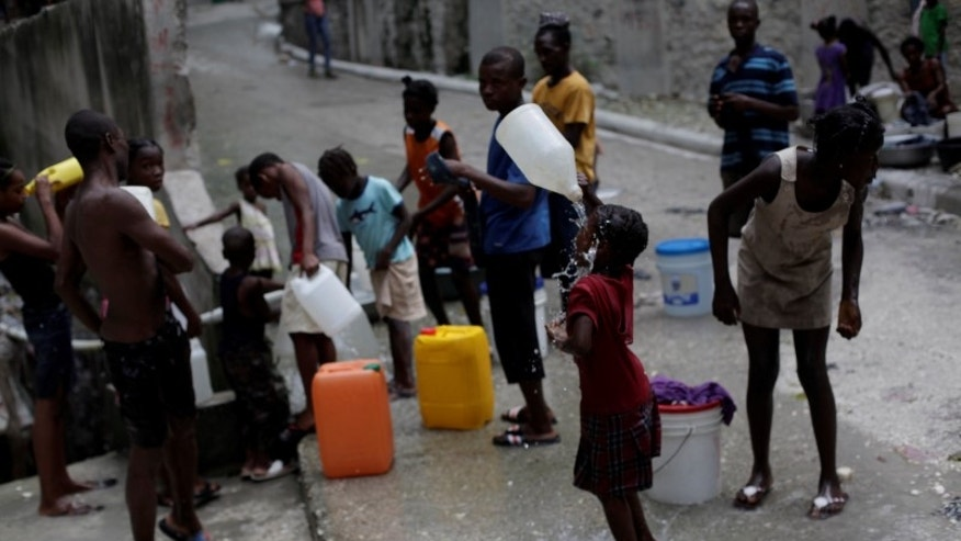 A girl cools off with drinkable water at a source in Port-au-Prince, Haiti