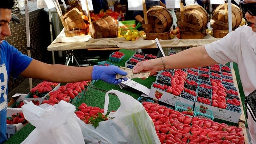 A shopper pays for fruit and assorted produce at a farmer's market in downtown Los Angeles.