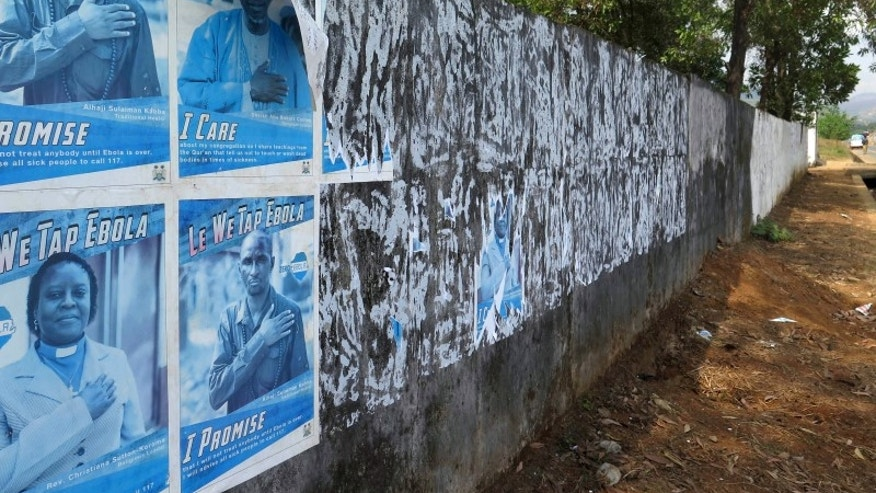 Ebola awareness posters are seen peeling off the wall in Freetown