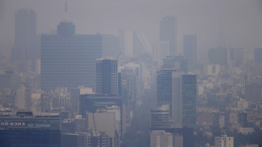 Buildings stand shrouded in smog in Mexico City.