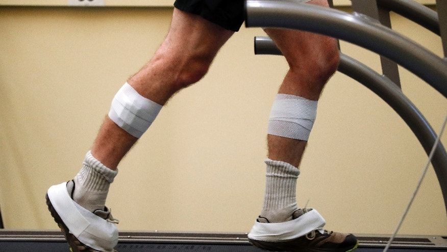 In this Friday, Aug. 12, 2016 photo, sensors are shown taped to the legs and feet of David Moran as he runs on a treadmill in Ann Arbor, Mich