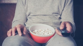 Young man is sitting on a sofa and eating popcorn while watching television