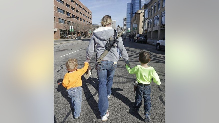 Gun rights activist Siri Davidson, center, has her AR15 slung on her back, as she walks with her children Keaton, 2, and Porter, 5, during a march for the 2nd Amendment rights Saturday, March 2, 2013, in Salt Lake City.