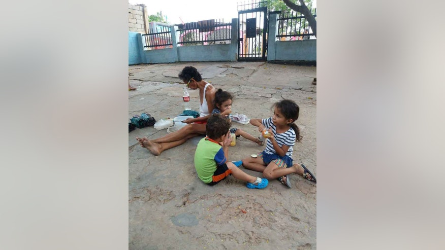 Maria del Carmen Chourio's family, which includes 11 children, playing outside their home in Maracaibo, Venezuela.