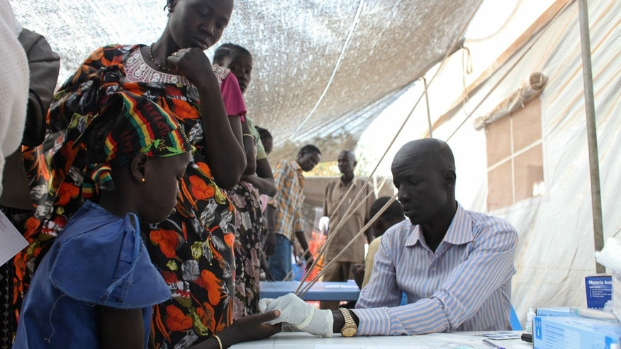 A displaced girl is tested for malaria at an MSF clinic in Tomping camp