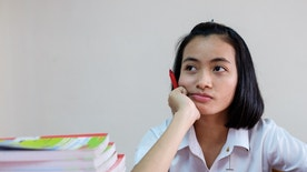 selective focus on thai young adult woman student in uniform reading a book in library with stress
