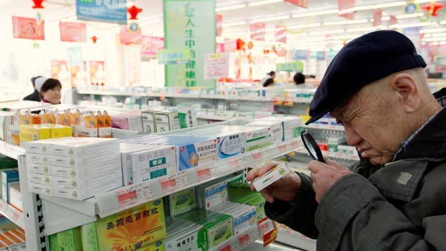 An elderly man uses a magnifiying glass to see the description on a pack of medicine at a pharmacy in Dandong