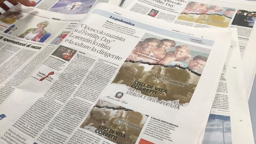 "A journalist lays out newspapers reporting the Italian Health Ministry's ""Fertility Day"" campaign ad showing four light-skinned adults at the beach illustrating ""good habits"" for reproductive health, over a group of young people, including a black man, smoking, in Rome, Thursday, Sept. 22, 2016. Italy's efforts to combat infertility and reverse one of Europe's lowest birthrates have stumbled with an ad campaign denounced as sexist, racist and ignorant of the economic reasons why Italians aren't having babies. The ad was removed by the ministry after being denounced as racist."