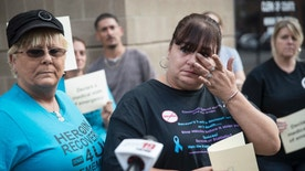 FILE - In this Sunday, Sept. 11, 2016, file photo, Christel Brooks, of Cincinnati, wipes a tear as she speaks to the media as heroin awareness and advocacy groups rally on the steps of the Hamilton County Justice Center to demand action after a wave of overdoses hit the region. Along with the tireless efforts by Ohio first responders to save heroin users, an increasing challenge with more powerful drugs showing up, some backlash is also showing up from people who question the resources being used to revive overdosed users and to try to get them into treatment. (AP Photo/John Minchillo, File)