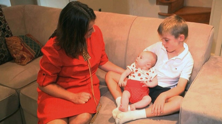 In this frame grab from video, taken Sept. 14, 2016, Sarah Gray with her son Callum, 6, and infant daughter Jocelyn in their Washington home. Callum's identical twin Thomas died of a birth defect when he was just 6 days old, and the family donated Thomas' eyes, liver and umbilical cord blood for medical research. Now Gray has written a book about her unusual journey to find out if that donation really made a difference, revealing a side of science laymen seldom glimpse. (AP Photo/Rick Gentilo)