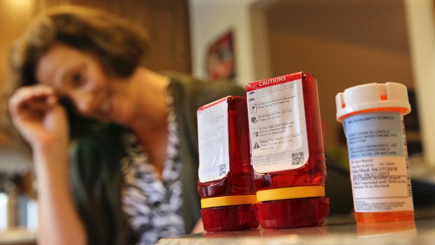 In this Sunday, Sept. 18, 2016, photo, Shelley Ewalt sits in her home, in Princeton, N.J., near an amber-colored CVS pharmacy prescription bottle, right, and two uniquely designed red ones from Target. After CVS took over operation of Target's drugstores earlier this year, distraught customers have been asking the drugstore chain to bring back the retailer's red prescription bottles, which came with color-coded rings, labeling on the top and prescription information that was easier to read. Ewalt tweeted to the drugstore chain, asking if there was any chance they might return to the design of the Target bottles, which she found easier to open.