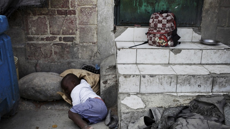A boy takes a nap on a street in Port-au-Prince, Haiti, February 24, 2016.