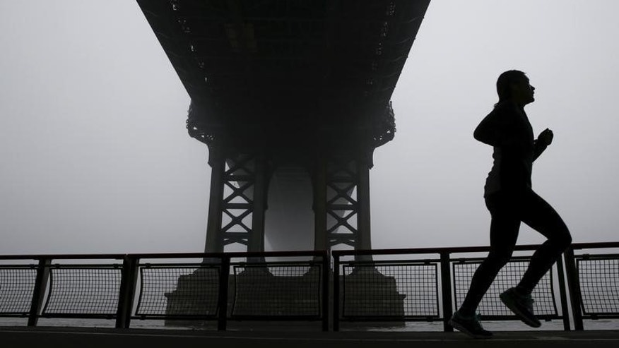 A woman is seen silhouetted while running under the fog covered Manhattan Bridge in New York