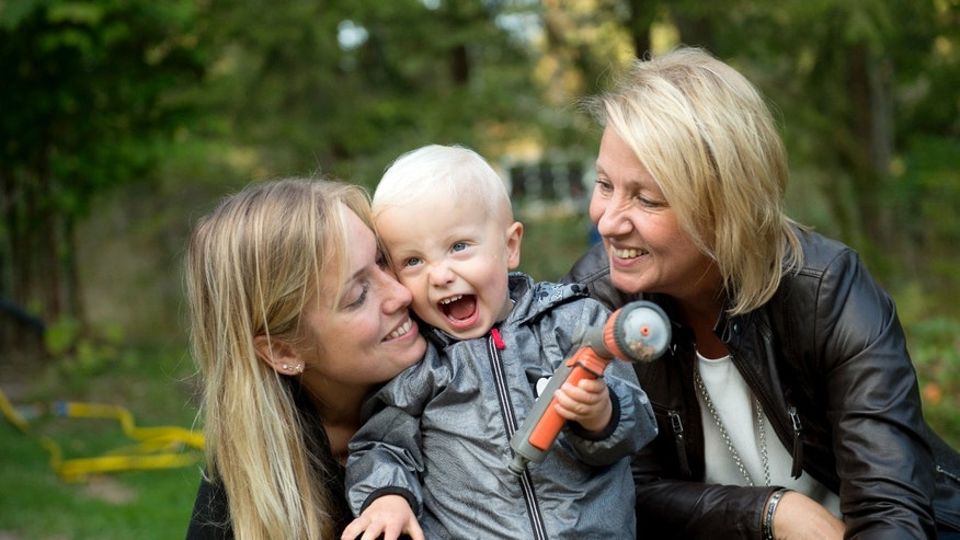 In this photo taken Tuesday, Sept. 20, 2016, Albin's mother Emelie Eriksson, left, poses for a photo with her son and her mother Marie, right, outside her home in Bergshamra, Sweden. For Emelie Eriksson, the bond she shares with her son Albin is particularly unique: both Emelie and Albin were born from the same womb, after Emelie received her mother's transplanted uterus in a revolutionary operation that links three generations of their family.  (AP Photo/ Niklas Larsson)