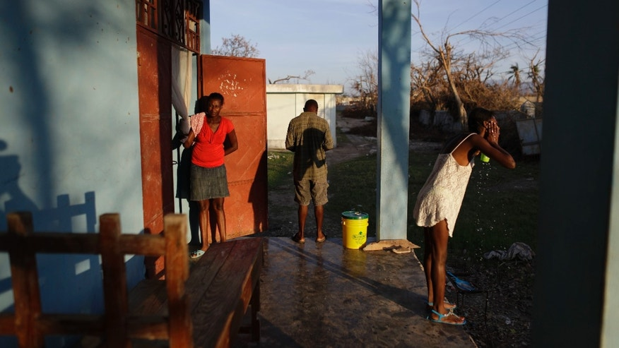 People whose homes were destroyed by Hurricane Matthew begin their day at a school where they have sought shelter in Port Salut, Haiti, Tuesday, Oct. 11, 2016. While some families like these were able to recover mattresses, furniture, and household goods from under the mud, others lost everything. The scores of people sheltering at this school have been told they have one more week before they have to move out so classes can restart. (AP Photo/Rebecca Blackwell)