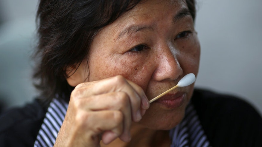 A mourner sniffs ammonia-soaked cotton wool handed out by medical rescue teams to help prevent fainting as she waits to pay her respects to Thailand's late King Bhumibol Adulyadej at the Grand Palace in Bangkok
